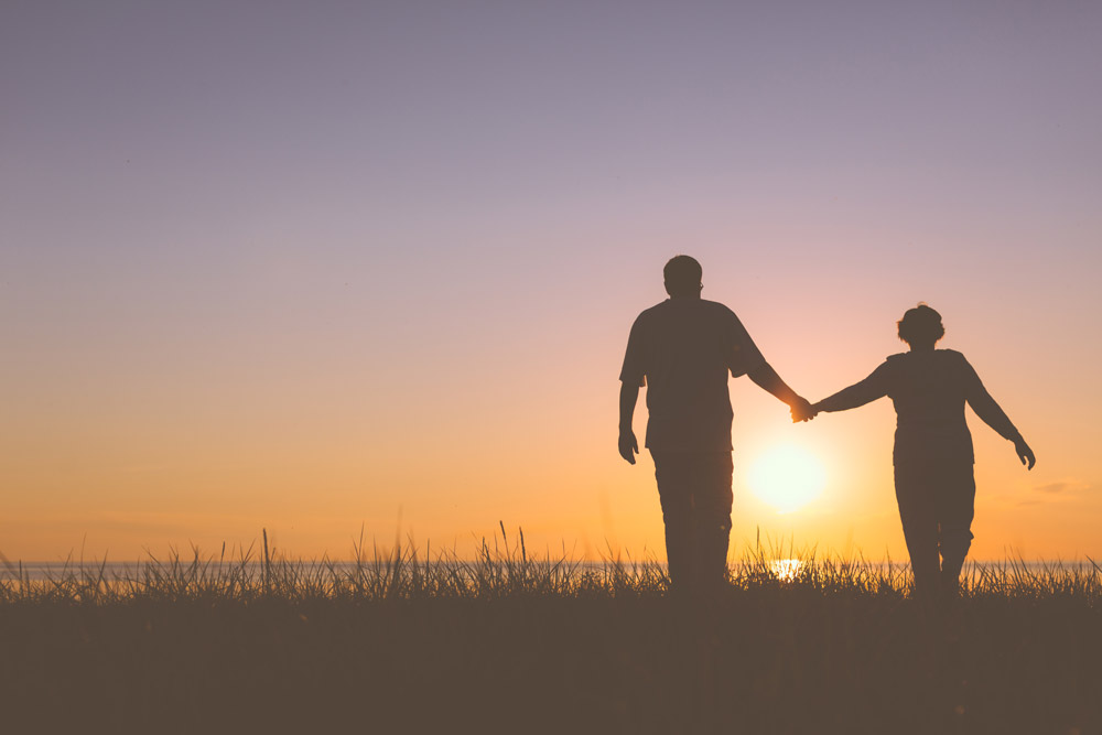 older-couple-walking-in-sunset
